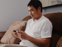 Source: freepik; Copyright: tirachardz; URL: https://www.freepik.com/free-photo/young-asian-man-using-mobile-phone-playing-video-games-television-living-room-male-feeling-happy-using-relax-time-lying-sofa-home-men-play-games-relax-home_6141928.htm#page=1&query=asian%20person%20using%20smartphone%20a; License: Licensed by JMIR.